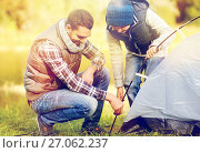 Купить «happy father and son setting up tent outdoors», фото № 27062237, снято 27 сентября 2015 г. (c) Syda Productions / Фотобанк Лори