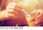 Купить «close up of woman hands with honey jar and spoon», фото № 27062257, снято 13 октября 2016 г. (c) Syda Productions / Фотобанк Лори