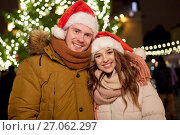 Купить «happy couple in santa hats at christmas tree», фото № 27062297, снято 2 декабря 2016 г. (c) Syda Productions / Фотобанк Лори