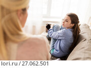 Купить «sad girl with smartphone looking at mother at home», фото № 27062501, снято 26 марта 2017 г. (c) Syda Productions / Фотобанк Лори
