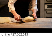 Купить «baker portioning dough with bench cutter at bakery», фото № 27062513, снято 15 мая 2017 г. (c) Syda Productions / Фотобанк Лори