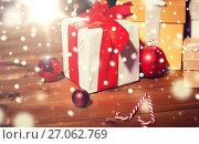 Купить «gifts, candies and christmas balls on wooden board», фото № 27062769, снято 1 октября 2015 г. (c) Syda Productions / Фотобанк Лори