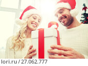 Купить «happy couple at home with christmas gift box», фото № 27062777, снято 8 октября 2015 г. (c) Syda Productions / Фотобанк Лори