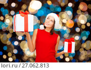 Купить «smiling woman in santa hat with christmas gifts», фото № 27062813, снято 15 августа 2013 г. (c) Syda Productions / Фотобанк Лори