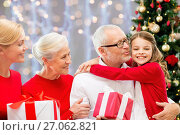 happy family with christmas gifts over lights. Стоковое фото, фотограф Syda Productions / Фотобанк Лори