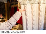Купить «woman buying woolen clothes at christmas market», фото № 27062889, снято 1 декабря 2016 г. (c) Syda Productions / Фотобанк Лори