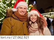 happy couple in santa hats at christmas tree. Стоковое фото, фотограф Syda Productions / Фотобанк Лори