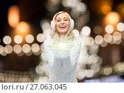 Купить «happy woman over christmas lights», фото № 27063045, снято 8 октября 2015 г. (c) Syda Productions / Фотобанк Лори