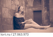 Купить «young female sitting barefoot near the stone wall», фото № 27063973, снято 20 июля 2019 г. (c) Яков Филимонов / Фотобанк Лори