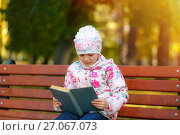 Купить «Ребенок увлечен книгой», фото № 27067073, снято 24 сентября 2017 г. (c) Иван Карпов / Фотобанк Лори