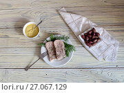 Sliced veal tongue on a white plate with dill, olives and sauce on a wooden table close-up. Стоковое фото, фотограф Татьяна Ляпи / Фотобанк Лори