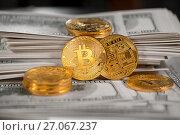 Золотые монеты криптовалюты биткойн лежат на стодолларовых пачках денег. Стоковое фото, фотограф Николай Винокуров / Фотобанк Лори