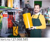 Купить «Happy guy deciding on best garden sprayer», фото № 27068585, снято 2 марта 2017 г. (c) Яков Филимонов / Фотобанк Лори