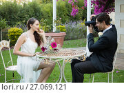 Купить «Bridegroom photographing bride while sitting at table in park», фото № 27069121, снято 2 мая 2017 г. (c) Wavebreak Media / Фотобанк Лори