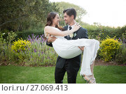 Купить «Bridegroom carrying bride while walking in park», фото № 27069413, снято 2 мая 2017 г. (c) Wavebreak Media / Фотобанк Лори