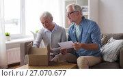 Купить «senior couple with parcel and delivery note», видеоролик № 27070677, снято 20 сентября 2017 г. (c) Syda Productions / Фотобанк Лори