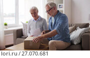 Купить «senior couple with delivery note opening parcel», видеоролик № 27070681, снято 20 сентября 2017 г. (c) Syda Productions / Фотобанк Лори