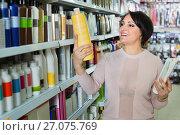 Купить «Happy pleasant woman choosing hair care products», фото № 27075769, снято 18 июля 2018 г. (c) Яков Филимонов / Фотобанк Лори