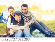 Купить «happy family with tablet pc and tent at camp site», фото № 27083293, снято 27 сентября 2015 г. (c) Syda Productions / Фотобанк Лори