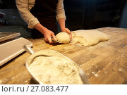 Купить «baker portioning dough with bench cutter at bakery», фото № 27083477, снято 15 мая 2017 г. (c) Syda Productions / Фотобанк Лори