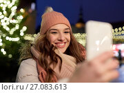 Купить «young woman taking selfie over christmas tree», фото № 27083613, снято 2 декабря 2016 г. (c) Syda Productions / Фотобанк Лори