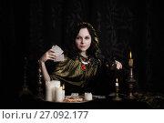 Купить «Young woman with divination cards in room», фото № 27092177, снято 5 марта 2017 г. (c) Майя Крученкова / Фотобанк Лори