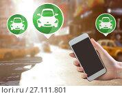 Купить «Hand holding phone with car icons in city», фото № 27111801, снято 28 марта 2020 г. (c) Wavebreak Media / Фотобанк Лори