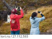Купить «Two hiking chinese women friends use smartphone taking photo in the autumn mountains», фото № 27112593, снято 11 октября 2017 г. (c) Константин Шишкин / Фотобанк Лори