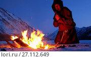 Купить «Alone monk in brown cloaks of the order of St. Francis is warming hands by the fire and prays», видеоролик № 27112649, снято 18 октября 2017 г. (c) Serg Zastavkin / Фотобанк Лори