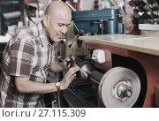 Купить «Portrait of diligent specialist sharpening steel knife», фото № 27115309, снято 16 декабря 2017 г. (c) Яков Филимонов / Фотобанк Лори