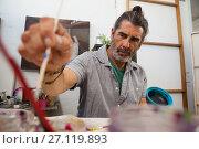 Купить «Attentive man painting bowl», фото № 27119893, снято 21 апреля 2017 г. (c) Wavebreak Media / Фотобанк Лори