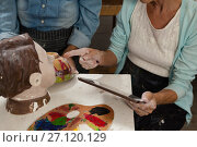 Купить «Woman using digital tablet while painting a sculptor», фото № 27120129, снято 21 апреля 2017 г. (c) Wavebreak Media / Фотобанк Лори