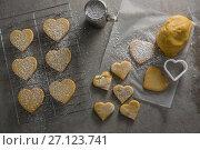Купить «Raw heart shape cookies on baking tray with flour shaker strainer, cookie cutter and wax paper», фото № 27123741, снято 5 мая 2017 г. (c) Wavebreak Media / Фотобанк Лори