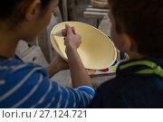 Купить «Female potter assisting her son in painting a bowl», фото № 27124721, снято 6 августа 2017 г. (c) Wavebreak Media / Фотобанк Лори