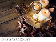 Lit candles and dry leaves on table. Стоковое фото, агентство Wavebreak Media / Фотобанк Лори