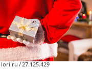 Купить «Santa claus hiding a gift box behind his back», фото № 27125429, снято 6 сентября 2016 г. (c) Wavebreak Media / Фотобанк Лори