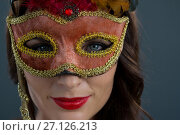 Купить «Woman wearing masquerade mask against black background», фото № 27126213, снято 22 мая 2017 г. (c) Wavebreak Media / Фотобанк Лори
