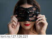 Купить «Woman wearing masquerade mask against black background», фото № 27126221, снято 22 мая 2017 г. (c) Wavebreak Media / Фотобанк Лори