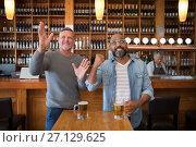 Купить «Friends watching football match while having beer in the restaurant», фото № 27129625, снято 22 августа 2017 г. (c) Wavebreak Media / Фотобанк Лори