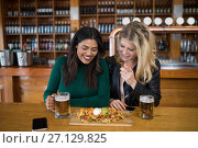 Купить «Two female friends having glass of beer and mexican food in bar», фото № 27129825, снято 22 августа 2017 г. (c) Wavebreak Media / Фотобанк Лори