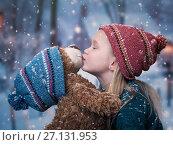 Купить «A little girl kisses a Teddy bear. snowing, winter», фото № 27131953, снято 15 ноября 2019 г. (c) Ирина Козорог / Фотобанк Лори