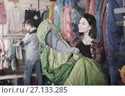 Купить «Ordinary female customer examining sleeping bags», фото № 27133285, снято 8 марта 2017 г. (c) Яков Филимонов / Фотобанк Лори