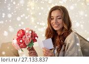 Купить «happy woman with flowers and greeting card at home», фото № 27133837, снято 15 октября 2016 г. (c) Syda Productions / Фотобанк Лори
