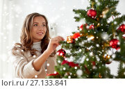 Купить «happy young woman decorating christmas tree», фото № 27133841, снято 15 октября 2016 г. (c) Syda Productions / Фотобанк Лори