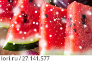 Купить «close up of watermelon slices over snow», фото № 27141577, снято 5 августа 2016 г. (c) Syda Productions / Фотобанк Лори