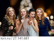 women with microphone singing karaoke at christmas. Стоковое фото, фотограф Syda Productions / Фотобанк Лори