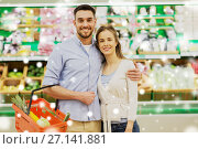 Купить «happy couple with food basket at grocery store», фото № 27141881, снято 21 октября 2016 г. (c) Syda Productions / Фотобанк Лори