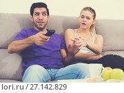 Woman trying to take away TV remote from boyfriend. Стоковое фото, фотограф Яков Филимонов / Фотобанк Лори