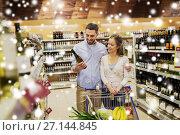 Купить «couple with wine and shopping cart at liquor store», фото № 27144845, снято 21 октября 2016 г. (c) Syda Productions / Фотобанк Лори
