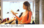 Купить «happy young woman choosing shoes at store», видеоролик № 27145673, снято 6 октября 2017 г. (c) Syda Productions / Фотобанк Лори